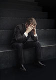 Giovane uomo d'affari che si siede sulle scale con la testa giù Fotografie Stock Libere da Diritti