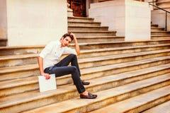 Giovane uomo d'affari che si siede sulle scale, rilassantesi fuori Fotografia Stock