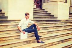 Giovane uomo d'affari che si siede sulle scale, rilassantesi fuori Immagini Stock Libere da Diritti
