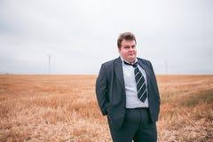 Giovane uomo d'affari che sta sul campo potato Fotografie Stock
