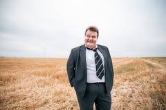 Giovane uomo d'affari che sta sul campo potato Fotografia Stock