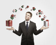Giovane uomo d'affari con i contenitori di regalo in sue mani. Immagini Stock