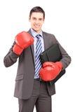 Giovane uomo d'affari con i guantoni da pugile rossi che tengono una cartella Immagine Stock