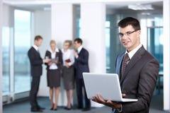 Giovane uomo d'affari con il computer portatile Fotografie Stock