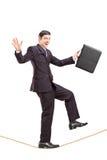 Giovane uomo d'affari con la cartella che cammina su una corda Immagine Stock Libera da Diritti