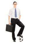 Giovane uomo d'affari con la cartella e calcio al di sotto del suo piede Fotografia Stock