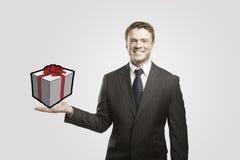 Giovane uomo d'affari con un regalo sulla sua mano. Fotografia Stock