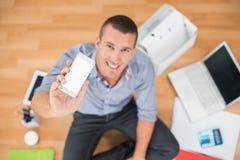Giovane uomo d'affari creativo che mostra il suo smartphone immagini stock libere da diritti