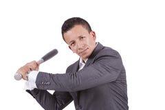 Giovane uomo d'affari della corsa mista che oscilla la sua mazza da baseball Fotografia Stock Libera da Diritti