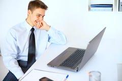 Giovane uomo d'affari di risata che esamina lo schermo del computer portatile Fotografia Stock Libera da Diritti