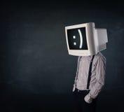 Giovane uomo d'affari divertente con un monitor sulla suoi testa e smiley sopra Immagine Stock