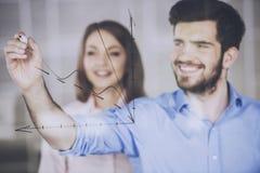 Giovane uomo d'affari e donna di affari che tracciano un grafico sullo schermo di vetro in ufficio fotografia stock