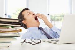 Giovane uomo d'affari esaurito che sbadiglia sul lavoro immagini stock