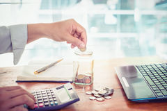 Giovane uomo d'affari facendo uso del calcolatore per i soldi di finanza, di imposta e di risparmio Fotografia Stock Libera da Diritti