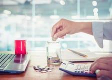 Giovane uomo d'affari facendo uso del calcolatore per i soldi di finanza, di imposta e di risparmio fotografie stock libere da diritti