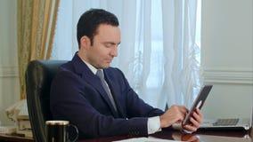 Giovane uomo d'affari facendo uso della compressa digitale moderna che cerca Internet archivi video