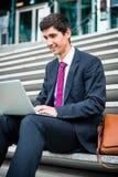 Giovane uomo d'affari facendo uso di un computer portatile mentre sedendosi all'aperto Fotografie Stock Libere da Diritti