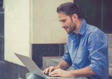 Giovane uomo d'affari felice bello che lavora al computer portatile all'aperto Fotografia Stock