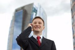 Giovane uomo d'affari felice che comunica sul telefono Immagini Stock