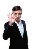 Giovane uomo d'affari felice che gesturing segno GIUSTO Immagini Stock