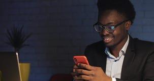 Giovane uomo d'affari felice che per mezzo dello smartphone al suo scrittorio all'ufficio di notte stock footage