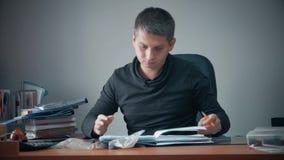 Giovane uomo d'affari felice che si siede nell'ufficio con le carte d'ufficio sulla tavola Funzionamento bello dell'uomo, scriven archivi video