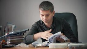 Giovane uomo d'affari felice che si siede nell'ufficio con le carte d'ufficio sulla tavola Funzionamento bello dell'uomo, scriven video d archivio