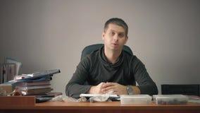 Giovane uomo d'affari felice che si siede nell'ufficio con le carte d'ufficio sulla tavola Funzionamento bello dell'uomo, scriven stock footage