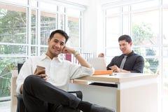 Giovane uomo d'affari felice che si siede nell'ufficio Succes o di affari immagine stock libera da diritti