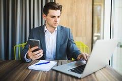Giovane uomo d'affari felice che sorride mentre leggendo il suo smartphone Ritratto del messaggio sorridente della lettura dell'u Fotografia Stock