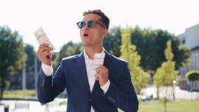 Giovane uomo d'affari felice che tiene una grande somma di denaro nelle suoi mani e dancing divertente Stile di affari, vincente, stock footage