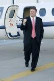 Giovane uomo d'affari felice davanti al jet corporativo Fotografia Stock Libera da Diritti