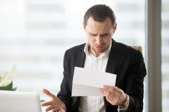 Giovane uomo d'affari frustrato che esamina lettera confusionaria in offi immagine stock