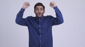 Giovane uomo d'affari indiano barbuto felice che ottiene buone notizie video d archivio