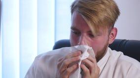 Giovane uomo d'affari malato che soffia il suo naso nel fazzoletto archivi video