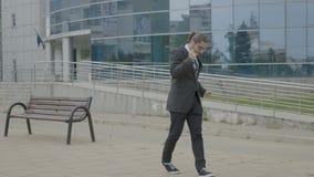 Giovane uomo d'affari moderno in vestito e legame che lascia lavoro e ballare divertente allegro sul suo modo di casa video d archivio