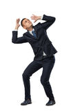 Giovane uomo d'affari nella posa difensiva impaurita di qualcosa isolato su fondo bianco Fotografie Stock
