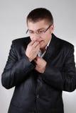 Giovane uomo d'affari nervoso che morde le sue barrette Immagine Stock Libera da Diritti