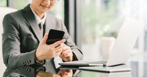 Giovane uomo d'affari o imprenditore che per mezzo dello smartphone, del computer portatile e della compressa digitale sul lavoro Fotografia Stock