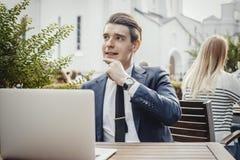 Giovane uomo d'affari pensieroso che si siede accanto al computer portatile e che tocca il suo pulcino immagini stock libere da diritti