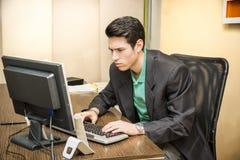 Giovane uomo d'affari serio che si siede allo scrittorio in ufficio Fotografie Stock