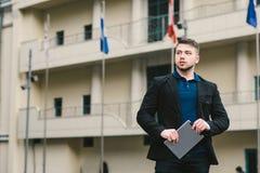 Giovane uomo d'affari serio con una compressa a disposizione contro lo sfondo di architettura e delle bandiere dei paesi differen Fotografia Stock