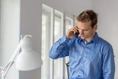 Giovane uomo d'affari serio impegnato in una conversazione importante facendo uso del suo Smart Phone immagini stock libere da diritti