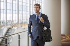 Giovane uomo d'affari sicuro all'hotel dal viaggio di affari della scala mobile Immagini Stock Libere da Diritti