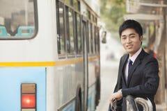 Giovane, uomo d'affari sicuro che aspetta alla fermata dell'autobus il bus a Pechino, Cina Immagini Stock