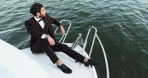 Giovane uomo d'affari sicuro su un yacht o su una barca contro un mare È soddisfatto con il successo nel suo affare ed nel suo stock footage