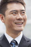 Giovane uomo d'affari Smiling e distogliere lo sguardo, ritratto Immagine Stock
