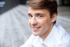 Giovane uomo d'affari sorridente in camicia bianca che si siede all'aperto immagini stock