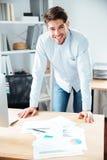 Giovane uomo d'affari sorridente che lavora con i documenti nel luogo di lavoro Immagini Stock Libere da Diritti