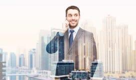 Giovane uomo d'affari sorridente che rivolge allo smartphone immagine stock libera da diritti